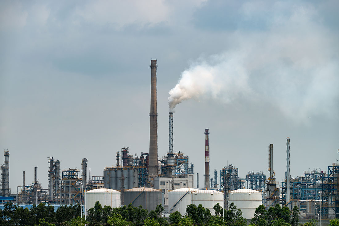Usine chimique avec des fumées sortant de cheminées représentant la pollution de l'air.