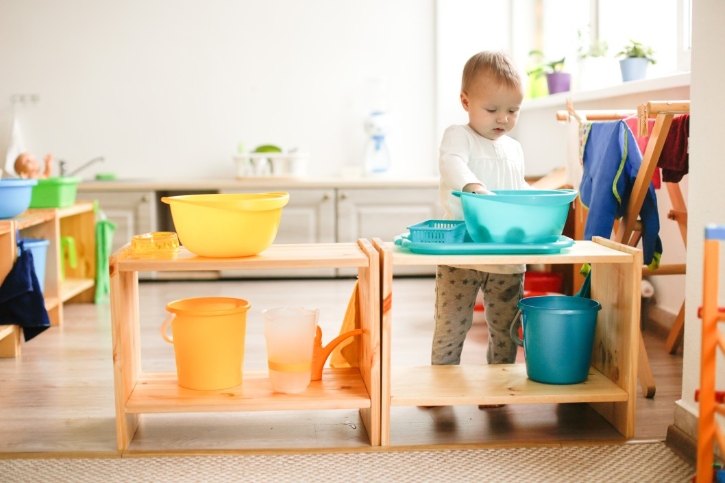 La petite enfance. Un petit enfant joue avec l'eau dans une bassine en plastique